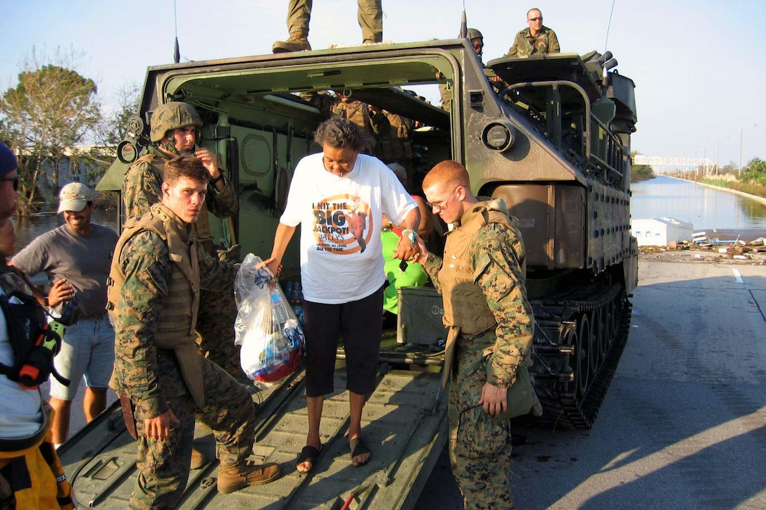 Marines assist Evelin Jenkins out of their assault amphibian vehicle in New Orleans, Sept. 7, 2005. Jenkins waited 8 days before agreeing to be evacuated from the ruins of Hurricane Katrina. Courtesy photo