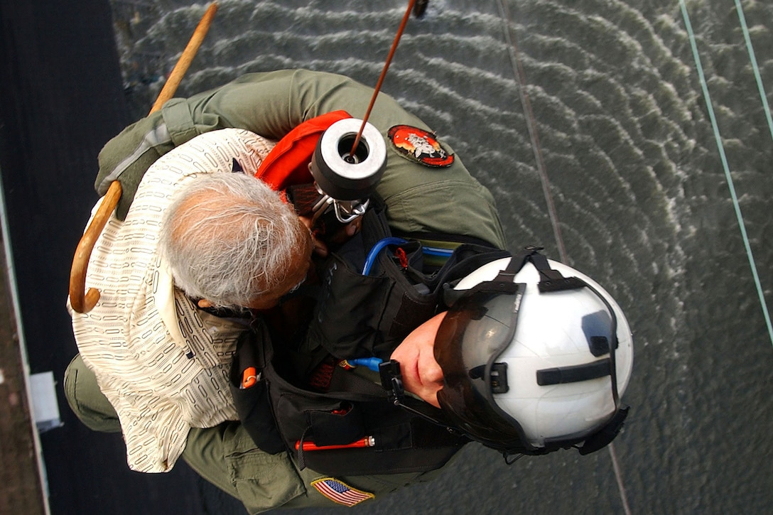 U.S. Navy Petty Officer 1st Class Tim Hawkins evacuates a victim of Hurricane Katrina from a rooftop into an SH-60B Seahawk helicopter in New Orleans, Sept. 5, 2005. Hawkins is a search-and-rescue  swimmer. U.S. Navy photo by Petty Officer 3rd Class Jay C. Pugh
