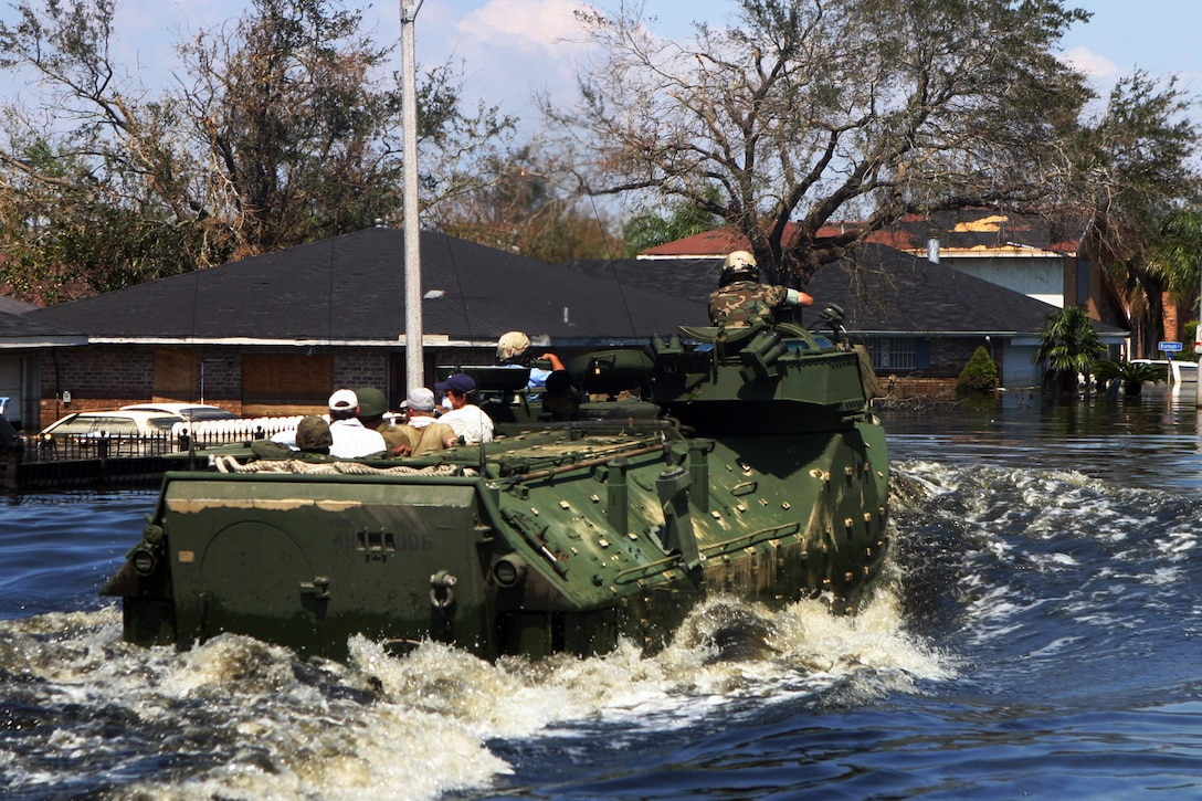Marines in amphibious vehicles and infantrymen travel down the decimated streets of Orleans Parish conducting search-and-rescue operations in New Orleans, Sept. 8, 2005. Some communities in the parish were under more than 10 feet of water. The Marines are assigned to the Special Purpose Marine Air Ground Task Force Katrina. U.S. Marine Corps photo by Cpl. Rocco DeFilippis