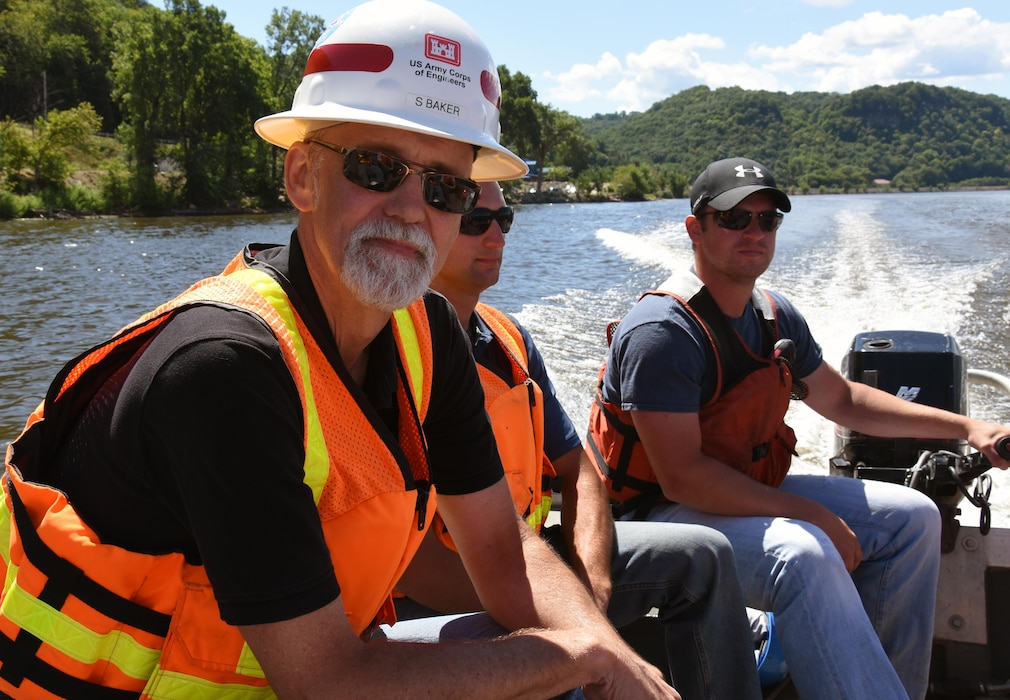 Resident engineer Scott Baker, center, during the weekly progress meeting and site visit  Aug. 11, 2015, for the Harper's Slough project. The Harper's Slough Habitat Rehabilitation and Enhancement Project, located within the Upper Mississippi River National Wildlife and Fish Refuge, was planned and designed under the authority of the Upper Mississippi River Restoration Program. It will protect five existing islands and construct an additional seven islands using material from the backwater and main channel. The program emphasizes habitat rehabilitation and enhancement projects and long-term resource monitoring. Project component includes dredging backwater areas and channels, constructing dikes, creating and stabilizing islands and controlling side channel flows and water levels. Once the project is completed, the project will be turned over to the U.S. Fish and Wildlife Service, who manages the refuge.
