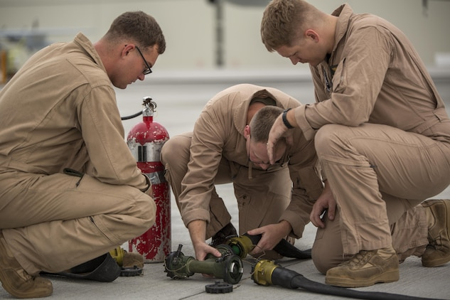 Cpl. Mason Stone, left, a KC-130J crewmaster, Staff Sgt. David Hoyt, middle, a KC-130J loadmaster, and Cpl. Greg Gambrell, a KC-130J crewmaster, set up the refueling site for air delivery ground refueling training aboard Marine Corps Air Station Iwakuni, Japan, Aug 20, 2015. Marine Aerial Refueler Transport Squadron 152 uses this training to make sure their Marines are able to proficiently use all of the KC-130J's assets.