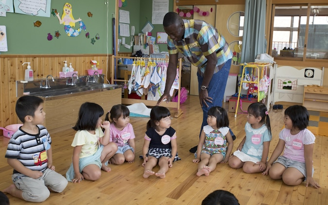 Lance Cpl. Derek Asiamah, a postal clerk with Headquarters and Headquarters Squadron based aboard Marine Corps Air Station Iwakuni, Japan, plays duck, duck, goose with students at Josho Hoikuen School in Iwakuni City as part of a community relations event hosted by the Marine Memorial Chapel, Aug. 11, 2015. Marine Memorial Chapel hosts community relations events that give volunteers the chance to be a positive role model for their Japanese neighbors and become a part of the community.