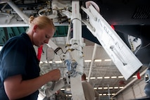 Staff Sgt. Keliah Easley, 757th Aircraft Maintenance Squadron Strike Aircraft Maintenance Unit F-15E Strike Eagle crew chief, installs a nose strut on an F-15E at Nellis Air Force Base, Nev., Aug. 19, 2015. The nose strut helps the front wheel from shimmying. (U.S. Air Force photo by Airman 1st Class Mikaley Towle)