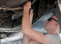 Senior Airman Shawn Lawson, 757th Aircraft Maintenance Squadron Strike Aircraft Maintenance Unit engine specialist, installs a flex strap on an F-15E Strike Eagle on the flightline at Nellis Air Force Base, Nev., Aug. 19, 2015. Strike AMU has approximately 170 Airmen working on 16 Strike Eagles. (U.S. Air Force photo by Airman 1st Class Mikaley Towle)