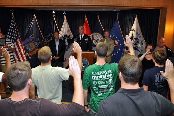Capt. Marcel Bolboaca-Negru, Operations Officer for the Buffalo Military Entrance Processing Station, is flanked by Congressmen Chris Collins (NY-27) (left) and Congressman Brian Higgins (NY-26) as he administers the Oath of Enlistment to several individuals at the Niagara Falls Air Reserve Station, N.Y. August 25, 2015.  These military service trainees will now journey to their respective basic training sites.  (U.S. Air Force photo by Master Sgt. Kevin Nichols)