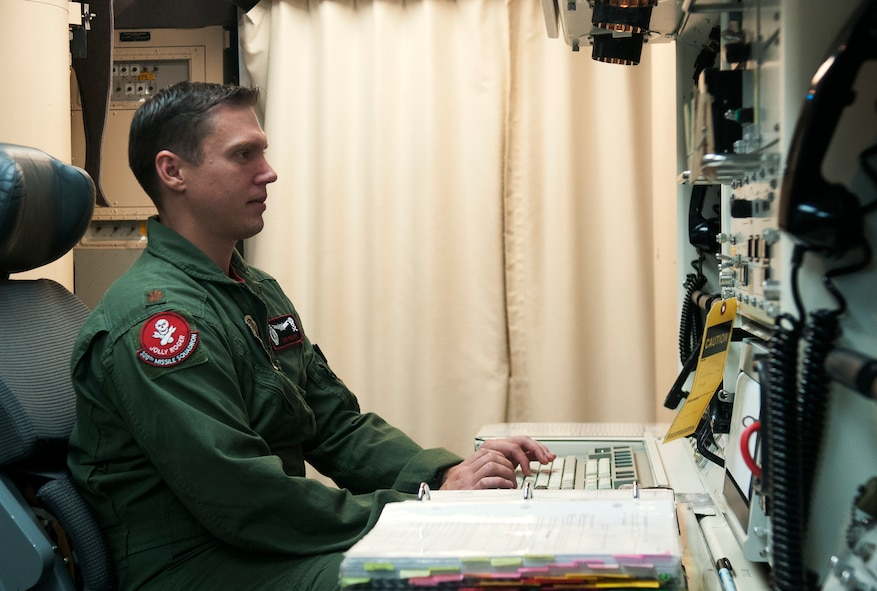 Maj. Tom Perry, 320th Missile Squadron missile combat crew member, checks his computer while on alert at the launch control center Aug. 21, 2015. Missileers use computers to check the status of the ICBMs under their command and ensure there are no issues with any of them. (U.S. Air Force by Airman 1st Class Brandon Valle)