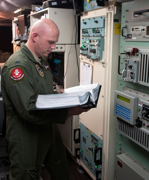 1st Lt. Jonathon Powell, 320th Missile Squadron missile combat crew member, reads from a technical order while checking equipment inside a launch control center Aug. 21, 2015. Technical orders help missileers perform task correctly and safely to prevent any accidents with equipment. (U.S. Air Force by Airman 1st Class Brandon Valle)