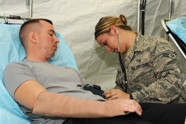 U.S. Air Force Airman 1st Class Kori Rosemann, 18th Medical Operations Squadron medical technician, checks the blood pressure of a mock patient following a simulated injury on Kadena Air Base, Japan, Aug. 18, 2015. Medical personnel assessed simulated injuries before loading them onto a C-130 for a simulated medical evacuation. (U.S. Air Force photo by Airman 1st Class Zade C. Vadnais)