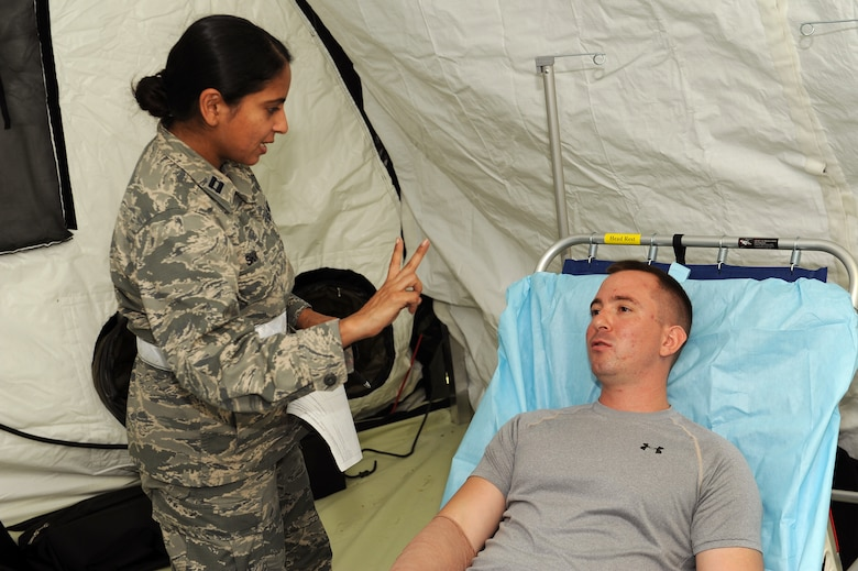 U.S. Air Force Capt. Pina Shah, 18th Medical Group clinical nurse, conducts a vision test on a mock patient to see how responsive he is after a simulated injury on Kadena Air Base, Japan, Aug. 18, 2015. Medical personnel from Misawa Air Base, Japan, Joint Base Lewis-McChord, Wash., and Camp Bullis, Texas supported the En-Route Patient Staging System exercise hosted by Kadena's 18th Wing. (U.S. Air Force photo by Airman 1st Class Zade C. Vadnais)