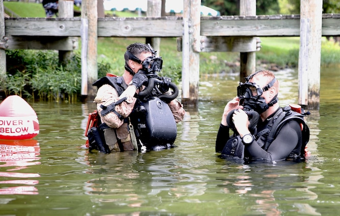 Gunnery Sgt. Zachary Burgart (left), project officer for amphibious reconnaissance equipment, and Master Sgt. Brad Colbert, project officer for small craft, MK25 closed-circuit underwater breathing apparatus. The system is a closed-circuit underwater breathing apparatus that allows its users to remain concealed in covert operations.