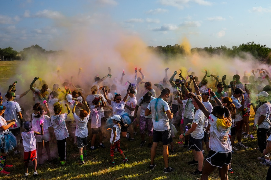 Sexual Assault Prevention and Response 5K Color Race participants dance and throw colored powder in the air to conclude the third annual race at Kiowa Trail on Goodfellow Air Force Base, Texas, Aug. 22. 2015. The SAPR Office hosts the event every year to promote sexual assault prevention awareness. (U.S. Air Force photo by Airman Caelynn Ferguson/Released)