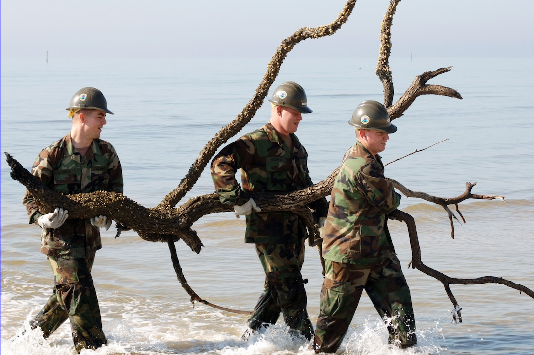 Navy personnel remove debris from ankle-deep water off the coast of Mississippi during the Great American Cleanup event in Biloxi, Miss., March 2, 2006.  Naval Mobile Construction Battalion-74 joined volunteers from the surrounding community and across the nation in a continuing effort to clean up and rebuild the Gulf Coast region following Hurricane Katrina in 2005. U.S. Navy photo by Petty Officer 1st Class Rob Wesselman