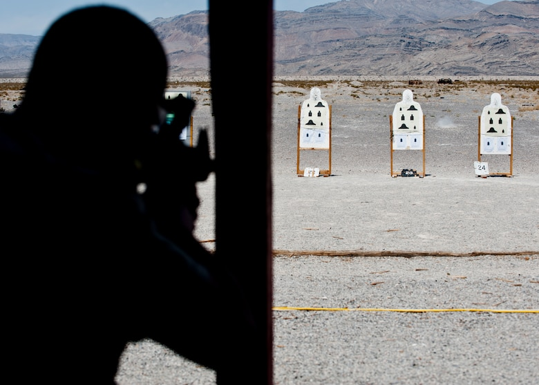 A participant in the M4 rifle qualification course fires his M4 at the 99th Security Forces Squadron Combat Arms Training and Maintenance firing range on Nellis Air Force Base, Nev., Aug. 18, 2015. Airmen aimed at six targets with three on each side designated for either iron sights or red dot sights to qualify on the M4 rifle. (U.S. Air Force photo by Airman 1st Class Jake Carter)