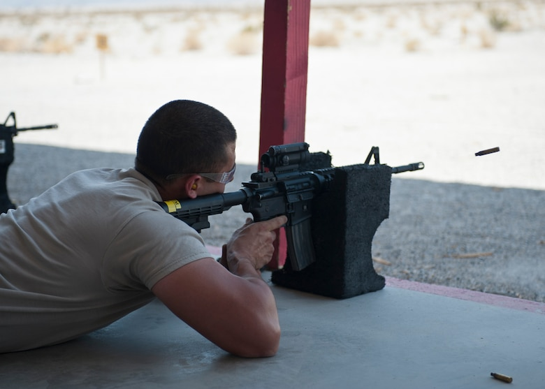 A participant in the M4 rifle qualification course fires his M4 at the 99th Security Forces Squadron Combat Arms Training and Maintenance firing range on Nellis Air Force Base, Nev., Aug. 18, 2015. Airmen switched between using iron sights and red dot sights to qualify for the M4 as they prepare to deploy, make a permanent change of station move, or satisfy yearly training requirements. (U.S. Air Force photo by Airman 1st Class Jake Carter)