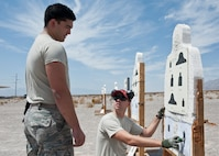 A combat arms instructor provides feedback to a participant in the M4 rifle qualification course at the 99th Security Forces Squadron Combat Arms Training and Maintenance firing range on Nellis Air Force Base, Nev., Aug. 18, 2015. To qualify for marksmanship, Airmen needed to hit 17 of 24 targets and to achieve expert, needed to hit 22 of 24. (U.S. Air Force photo by Airman 1st Class Jake Carter)