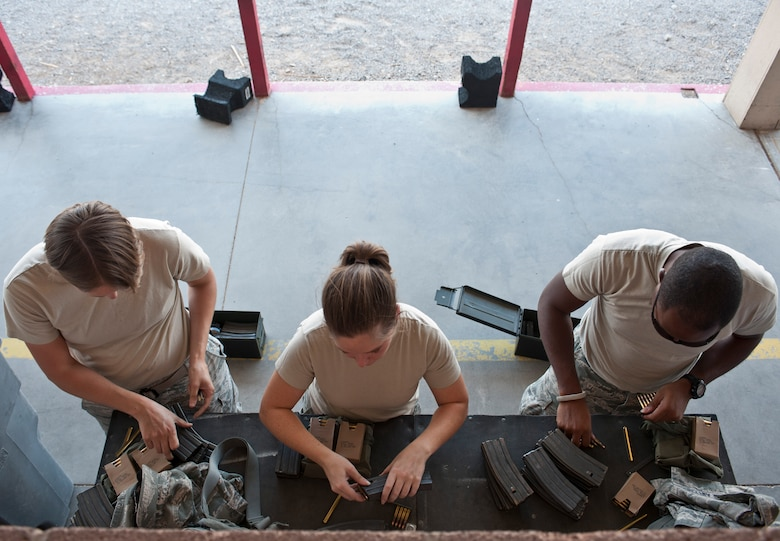 Participants in the M4 rifle qualification course load ammunition into their respective cartridges at the 99th Security Forces Squadron Combat Arms Training and Maintenance firing range on Nellis Air Force Base, Nev., Aug. 18, 2015. Airmen participated in the qualification course in preparation for either a deployment, permanent change of station move, or part of yearly training. (U.S. Air Force photo by Airman 1st Class Jake Carter)