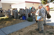 Oregon Air National Guard Chief Master Sgt. Larry Keller, assigned to the 142nd Fighter Wing Logistics Readiness Squadron, left, give instructions to other Airmen waiting to loading buses at the Portland Air National Guard Base, Ore., as they depart for firefighter training in Salem, Ore., Aug. 25, 2015. The personnel are scheduled to report to the Department of Public Safety Standards and Training (DPSST), in Salem, Oregon to undergo firefighting training starting Wednesday, Aug. 26. DPSST officials say the additional group should complete their training by Aug. 30. (U.S. Air National Guard photo by Tech. Sgt. John Hughel, 142nd Fighter Wing Public Affairs/Released)