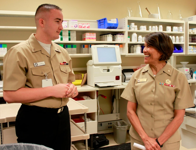 Hospitalman Dalton Terrell, pharmacy technician, Naval Health Clinic Charleston, describes the daily operations of and services provided at NHCC's pharmacy, for Rear Adm. Raquel Bono, chief, Navy Medical Corps and director, National Capital Region Medical Directorate , Aug. 21, 2015 during Bono's visit to NHCC. Bono also met with NHCC command leadership, visited various departments throughout the clinic, and spoke with staff members about the future of Navy medicine and what's on the horizon for military health care through the collaboration of joint service operations. (Navy photo/ Hospitalman Mark Simon)