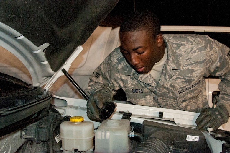 Senior Airman Joseph Bates, 90th Logistics Readiness Squadron Traffic Control Function controller, checks a vehicle's fluid levels Aug. 5, 2015, on F.E. Warren Air Force Base, Wyo. Bates and his fellow TCF controllers often help out day shift vehicle operations Airmen by checking vehicles in addition to their TCF duties. (U.S. Air Force photo by Senior Airman Jason Wiese)