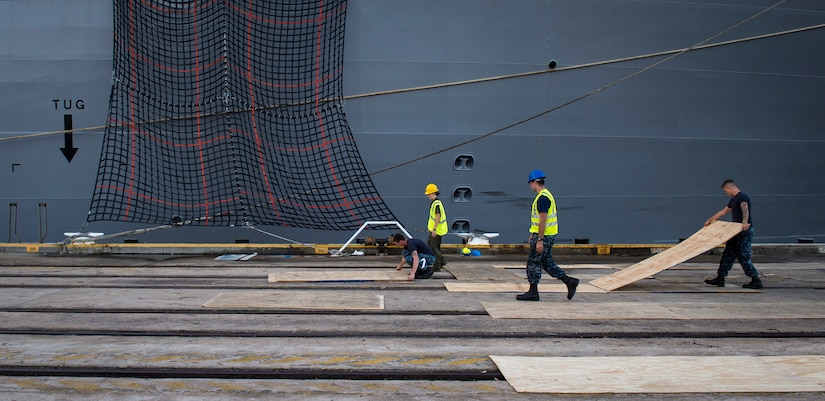 Sailors, Marines and civilians with the Navy Munitions Command Unit Charleston and Marine Corps Systems Command prepare the loading zone for uploading cargo to the USNS Lewis and Clark (T-AKE-1) March, 25, 2015, at Naval Weapons Station Wharf Alpha, Charleston, S.C. The Lewis and Clark is a replenishment naval vessel. In 2012, USNS Lewis and Clark became one of 12 ships that comprise the United States Marine Corps Maritime Prepositioning Program. Prepositioning ships provides quick and efficient movement of military equipment/supplies between operating areas without reliance on other nations' transportation networks. These ships assure U.S. regional combatant commanders they will have what they need to quickly respond in a crisis - anywhere, anytime. (U.S. Air Force photo/Airman 1st Class Clayton Cupit)