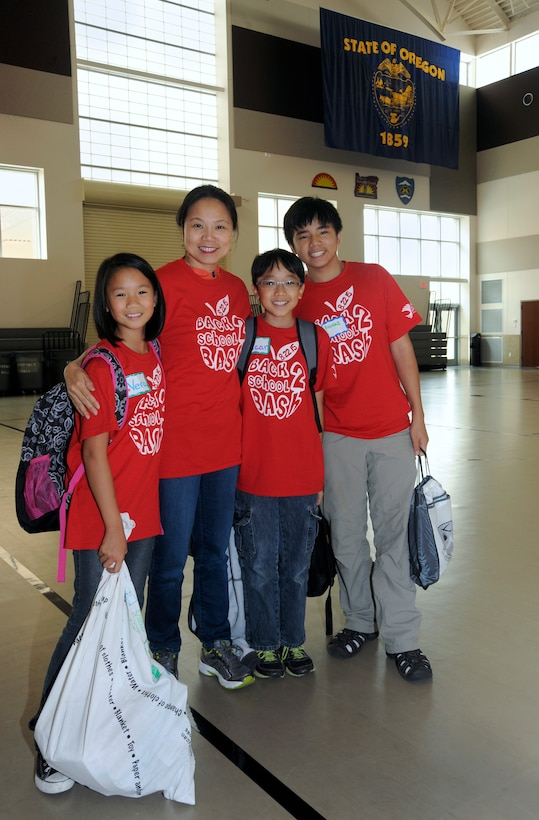 Lt. Col Thuy Tran, an Optometrist with the 142nd Fighter Wing Medical Group, along with her children, pause for a family photograph as the Back2School Bash concludes at Camp Withycombe, Ore., Aug. 22, 2015. (U.S. Air National Guard photo by Tech. Sgt. John Hughel, 142nd Fighter Wing Public Affairs/Released)