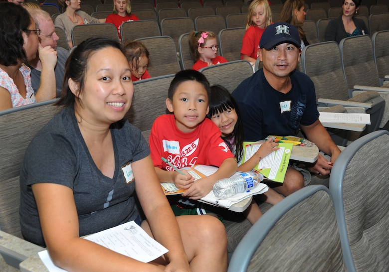 Air National Guard Master Sgt. Todd Le and his family review materials as the Back2School Bash concludes, Aug. 22, 2015, Camp Withycombe, Ore. (U.S. Air National Guard photo by Tech. Sgt. John Hughel, 142nd Fighter Wing Public Affairs/Released)