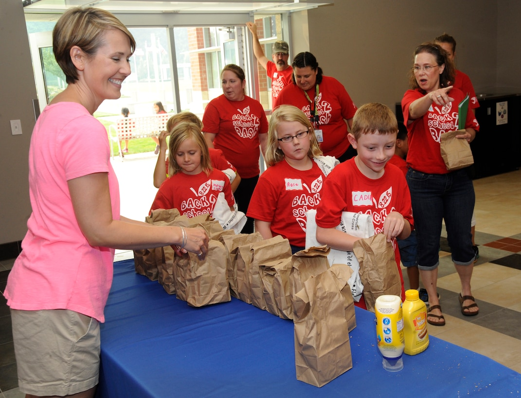 Volunteers from the United States Organization (USO) hand out sack lunches to participates at the Back2School Bash, Aug. 22, 2015, Camp Withycombe, Ore. (U.S. Air National Guard photo by Tech. Sgt. John Hughel, 142nd Fighter Wing Public Affairs/Released)
