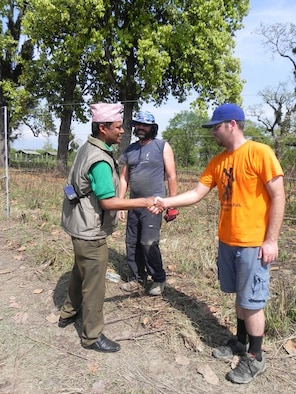 Kamal Jung Kunwar, chief conservation officer and author, greets U.S. Air Force Tech. Sgt. Scott Bettencourt, a pharmacy flight chief with the 55th Medical Support Squadron, while visiting with volunteers building working elephant corrals in Chitwan National Park, Nepal.  An international crew of volunteers came to Chitwan to build the corrals that will replace the chains elephants were tethered to in their off time. (photo courtesy of Elephant Aid International)