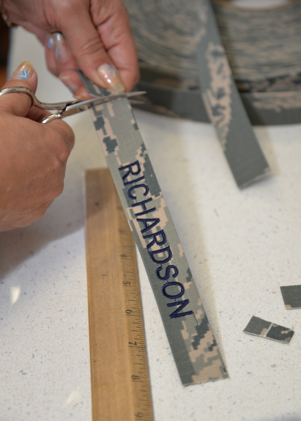 Sarah Jakes, 100th Force Support Squadron Arts and Crafts embroiderer from Mildenhall, Suffolk, finishes name tapes for a customer Aug. 20, 2015, on RAF Mildenhall, England. Additionally, Jakes embroiders clothing, baseball caps and other similar items. The 100th FSS facility can frame photos and other items for customers, engrave onto products made of materials such as glass, wood and slate, and create unique items for leaving gifts or awards. (U.S. Air Force photo by Karen Abeyasekere/Released)