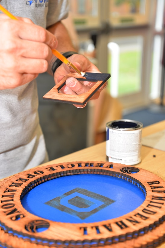 """Stephen Fournier, 100th Force Support Squadron Arts and Crafts staff member from Richlands, N.C., paints wood used to form the background of the """"Square D"""" on a 3-D wood plaque for a customer Aug. 20, 2015, on RAF Mildenhall, England. Using a laser machine, Fournier is able to transform wood into unique leaving gifts, awards or personal gifts. (U.S. Air Force photo by Karen Abeyasekere/Released)"""