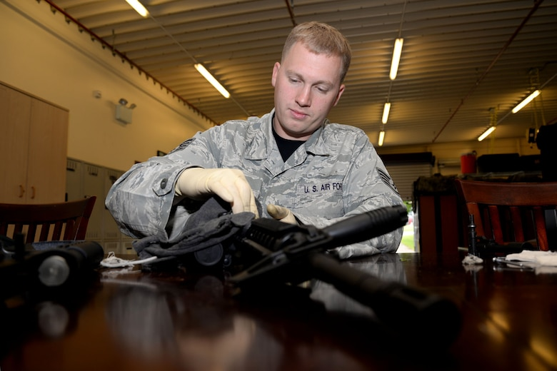 U.S. Air Force Staff Sgt. Daniel Henderson, 352nd Special Operations Support Squadron Deployed Aircraft Ground Response Element team member from Richfield, Utah, cleans a rifle during routine maintenance Aug. 21, 2015, on RAF Mildenhall, England. Henderson was selected for the Square D Spotlight for portraying the core value of Excellence in All We Do. (U.S. Air Force photo by Senior Airman Kate Thornton/Released)
