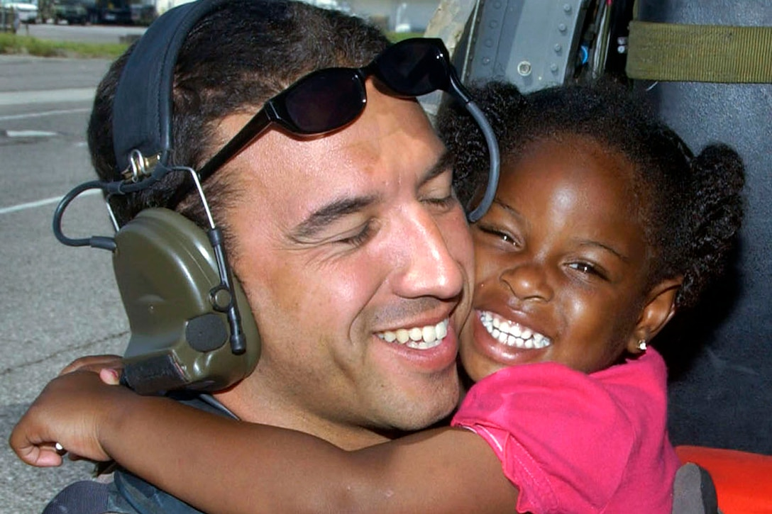 A young Hurricane Katrina survivor hugs her rescuer, Air Force Staff Sgt. Mike Maroney, after she was relocated to the New Orleans International Airport in New Orleans, Sept. 7, 2005. Maroney is a pararescueman assigned to the 58th Rescue Squadron on Nellis Air Force Base. The Air Force Special Operations Command and various Guard rescue squadrons worked together to aid in rescue efforts of Hurricane Katrina victims. U.S. Air Force P\photo by Airman 1st Class Veronica Pierce