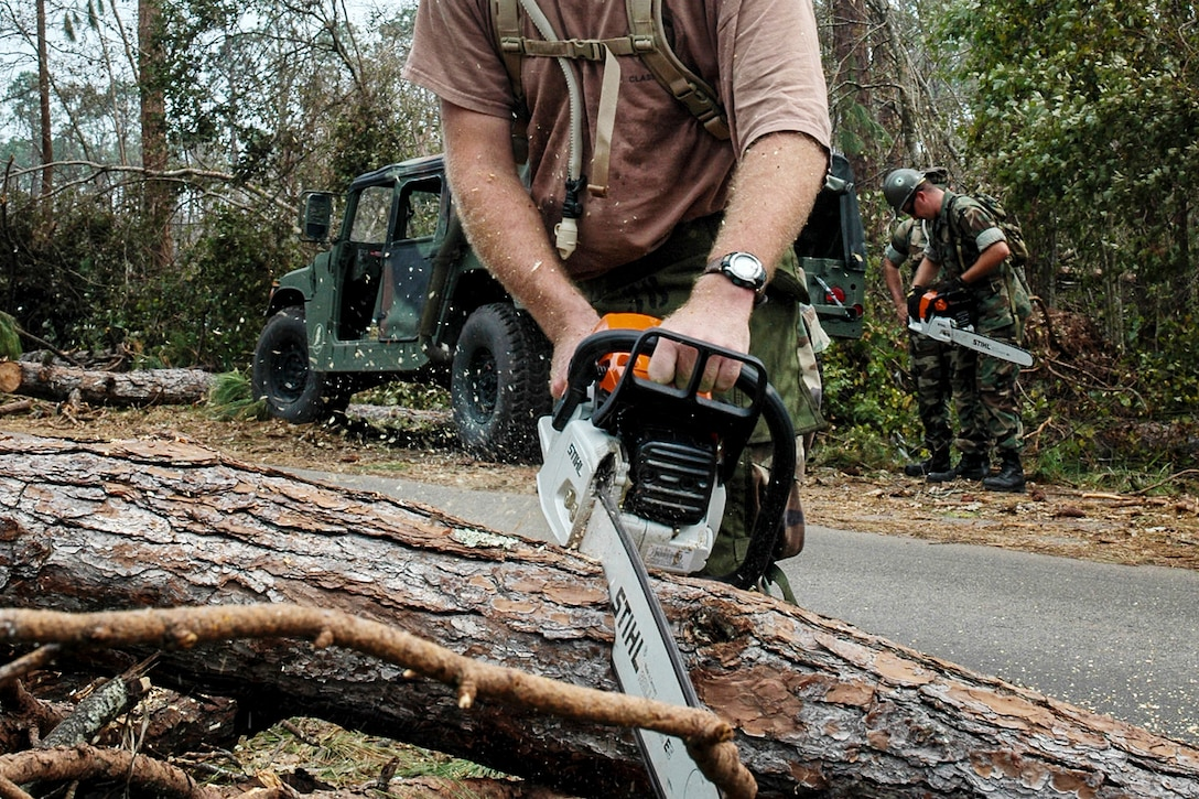 A Navy Seabee uses a chainsaw to remove fallen trees in Gulfport, Miss, Aug. 31, 2005, in the aftermath of Hurricane Katrina. U.S. Navy photo by Petty Officer 3rd Class Ja'lon A. Rhinehart