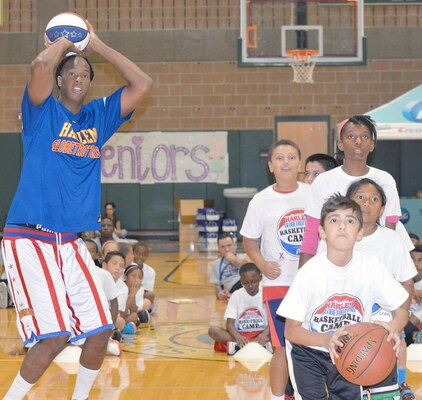 "Jermaine ""Stretch"" Middleton shoots baskets with children during a basketball camp held at Cole High School on JBSA-Fort Sam Houston Aug. 19."