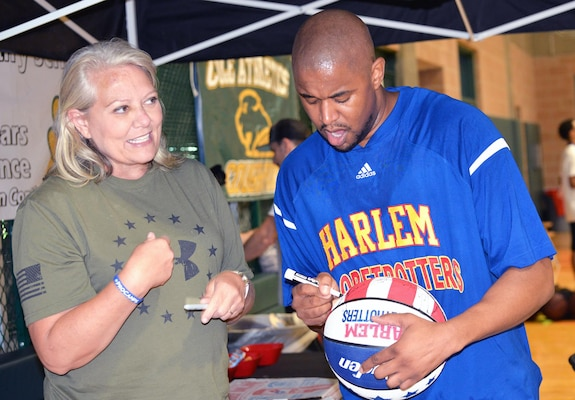 "Harlem Globetrotters Shane ""Scooter"" Christensen autographs a ball for Simone Larson during a basketball camp held at Cole High School on JBSA-Fort Sam Houston Aug. 19."