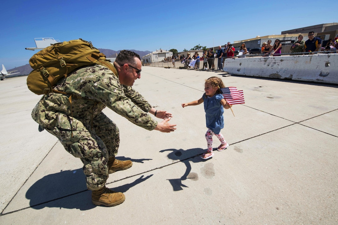 U.S. Navy Petty Officer 2nd Class Brandin Salazar greets his daughter on the flightline on Naval Base Ventura County following his return from deployment on Naval Base Ventura County, Calif., Aug. 26, 2015.  Salazar is a steelworker assigned to Naval Mobile Construction Battalion 5, which conducted maintenance and infrastructure improvements at U.S. military facilities in the U.S. Pacific Command area of operations. U.S. Navy photo by Chief Lowell Whitman