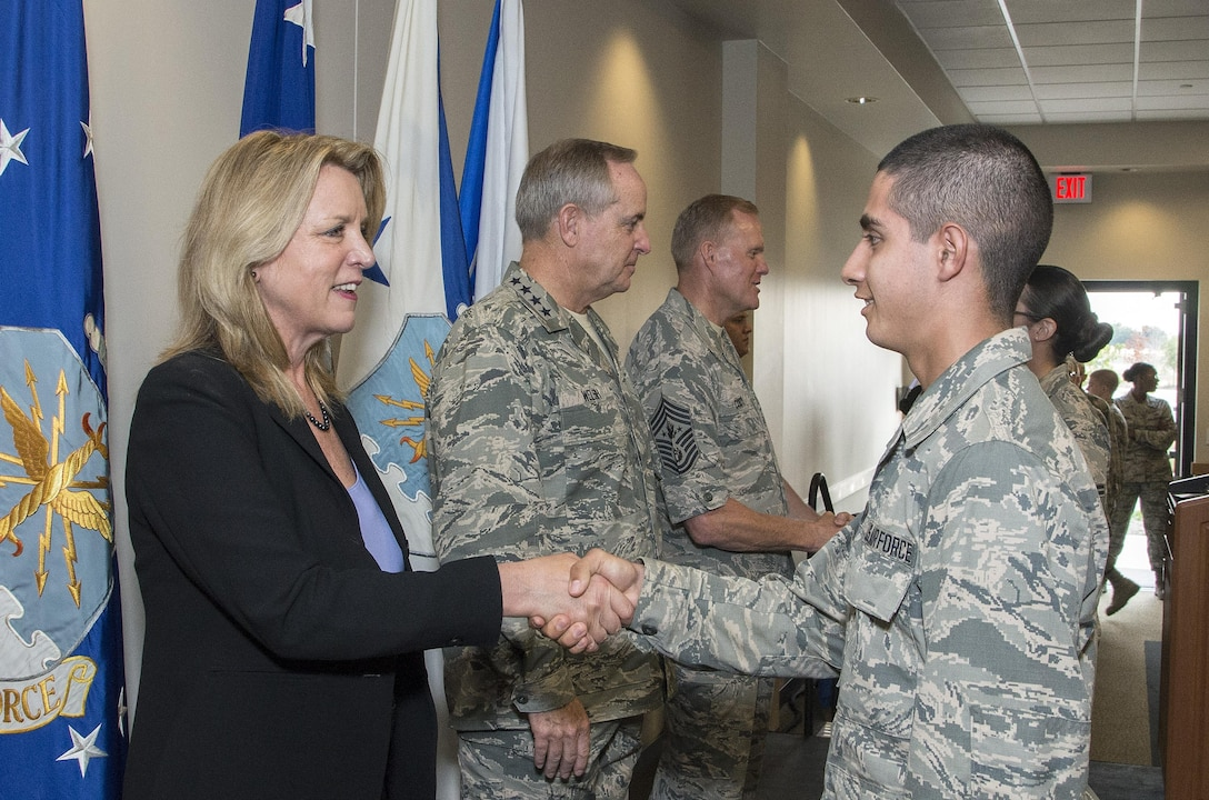 """Secretary of the Air Force Deborah Lee James, Air Force Chief of Staff General Mark A. Welsh III and Chief Master Sergeant of the Air Force James A. Cody congratulate Airmen who will soon complete Airmen's Week Aug. 27, 2015, at Joint Base San Antonio-Lackland's Pfingston Reception Center. The Airmen received a copy of """"America's Air Force: A Profession of Arms,"""" the next evolution of the """"Little Blue Book"""" previously released in 1997. The new book gives Airmen instant access to the core values, codes and creeds that guide Airmen as they serve in the Profession of Arms. The book will be distributed to all new Airmen before transitioning to technical training and available online through Air Force e-publishing."""