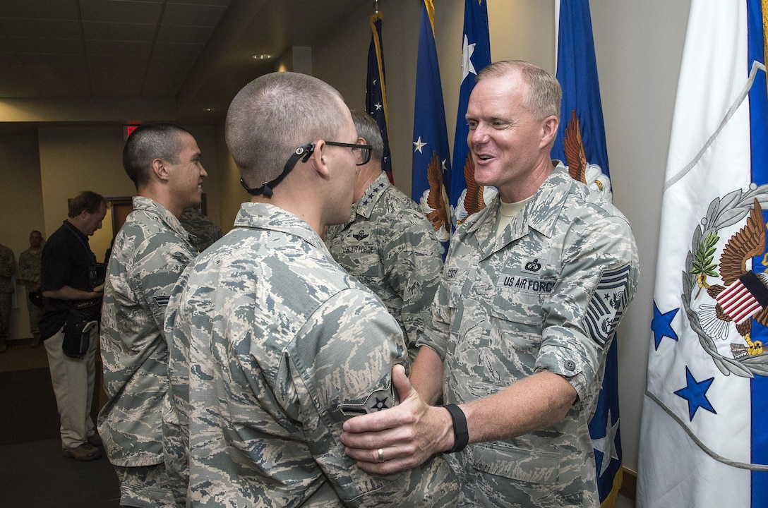 """Chief Master Sergeant of the Air Force James A. Cody congratulates an Airman attending Airmen's Week Aug. 27, 2015, at Joint Base San Antonio-Lackland's Pfingston Reception Center. The Airmen received a copy of """"America's Air Force: A Profession of Arms,"""" the next evolution of the """"Little Blue Book"""" previously released in 1997. The new book gives Airmen instant access to the core values, codes and creeds that guide Airmen as they serve in the Profession of Arms. The book will be distributed to all new Airmen before transitioning to technical training and available online through Air Force e-publishing."""