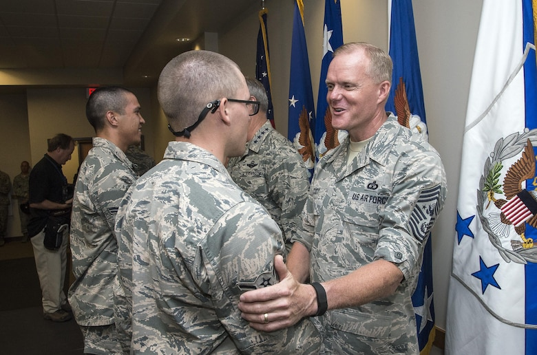 "Chief Master Sergeant of the Air Force James A. Cody congratulates an Airman attending Airmen's Week Aug. 27, 2015, at Joint Base San Antonio-Lackland's Pfingston Reception Center. The Airmen received a copy of ""America's Air Force: A Profession of Arms,"" the next evolution of the ""Little Blue Book"" previously released in 1997. The new book gives Airmen instant access to the core values, codes and creeds that guide Airmen as they serve in the Profession of Arms. The book will be distributed to all new Airmen before transitioning to technical training and available online through Air Force e-publishing."