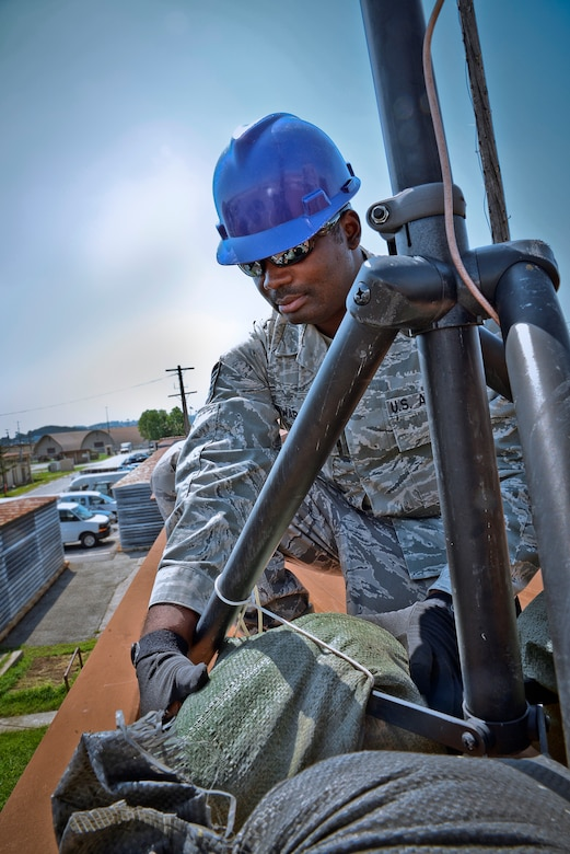 Tech. Sgt. Olandre L. Edwards, 644th Combat Communications Squadron radio frequency transmissions supervisor, adjusts sand bags on an antenna stand as part of a preventative-maintenance inspection to ensure reliable radio communications are maintained Aug. 27, 2015, at Suwon Air Base, Republic of Korea. The 644th CBCS is in place at Suwon AB from Andersen Air Force Base, Guam, to help set up and maintain temporary communications. (U.S. Air Force photo/Tech. Sgt. Travis Edwards)