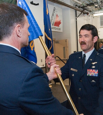 Lt. Col. Matthew Komatsu, a combat rescue officer with the Alaska Air National Guard's 212th Rescue Squadron, recieves his unit's command flag from Lt. Col. Tom Bolin, commander of the 176th Operations Group, in a ceremony on Joint Base Elmendorf-Richardson Aug. 27, 2015.  A veteran of multiple deployments, Komatsu had been serving as the squadron's director of operations. National Guard photo by Capt. John Callahan.