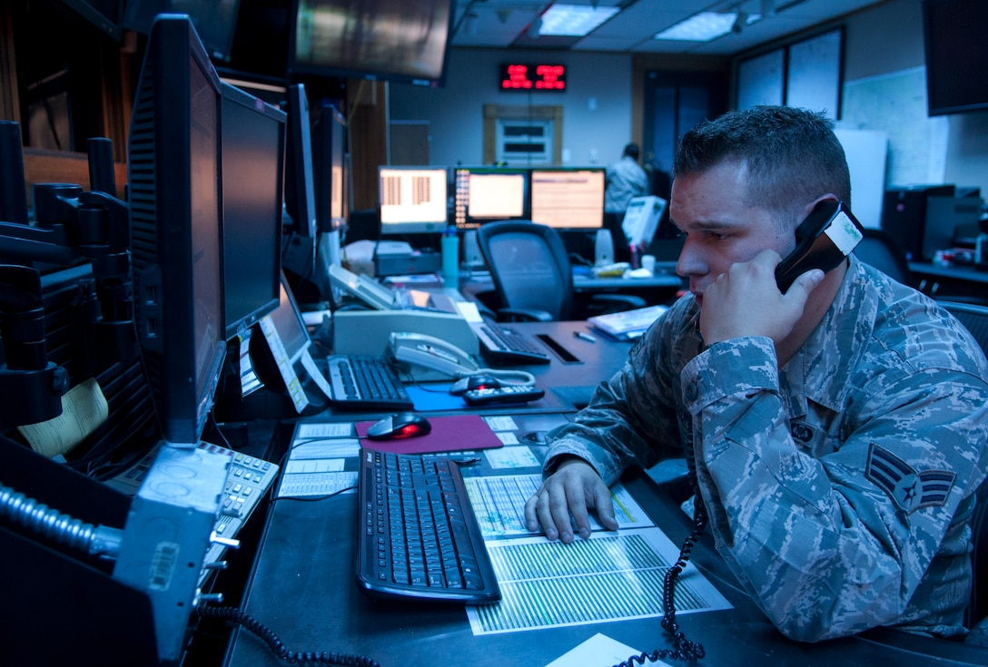 Senior Airman Zachary Pirrung, 90th MW Command Post senior emergency action controller, provides detailed information to help keep the mission of Warren efficient, Aug. 25, 2015, in the command post. Pirrung along with Airman 1st Class Chanel Cummings, 90th MW Command Post junior emergency action controller, were tasked with keeping information flowing to the appropriate shops and leadership through the night if the need arises. (U.S. Air Force photo by Airman 1st Class Malcolm Mayfield)