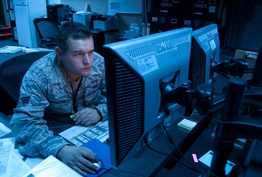 Senior Airman Zachary Pirrung, 90th MW Command Post senior emergency action controller, mans the command post at 12:54 a.m., Aug. 25, 2015. Pirrung was one half of the two-person team making up the night shift. A minimum of two individuals are required to always be available in the office 24/7, 365 days a year. (U.S. Air Force photo by Airman 1st Class Malcolm Mayfield)