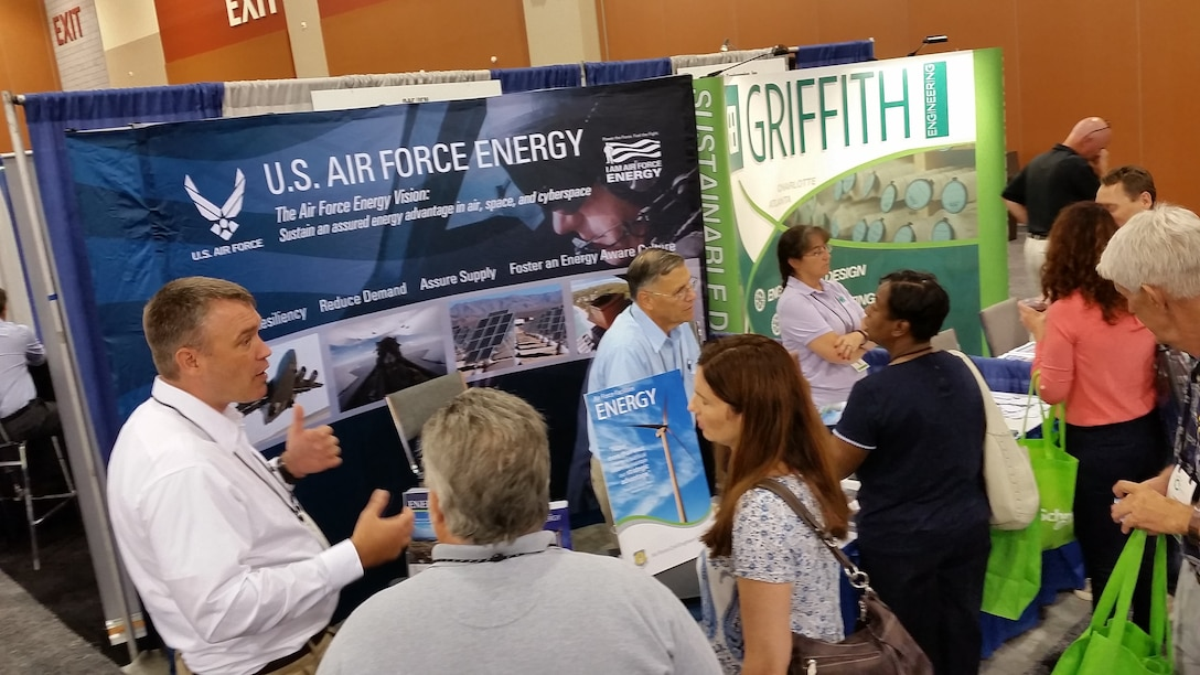 """From left, AFCEC energy engineers Dan Gerdes, Dick Fillman and Lucy Notestine interact with attendees at the Department of Energy's """"Energy Exchange"""" conference in Phoenix, Aug. 10. (U.S. Air Force photo/Kevin Elliott/Released)"""