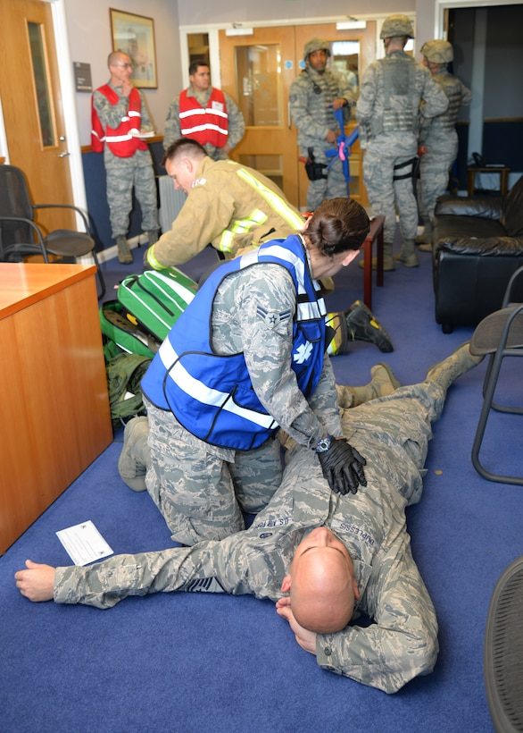 Airmen from the 100th Civil Engineer Squadron Fire Department and 48th Medical Group respond to a simulated victim during an active shooter exercise as 100th Air Refueling Wing inspection team members evaluate the situation Aug. 25, 2015, on RAF Mildenhall, England. As part of an emergency lockdown exercise, an armed assailant was on base testing service members' reactions to the scenario. (U.S. Air Force photo by Karen Abeyasekere/Released)