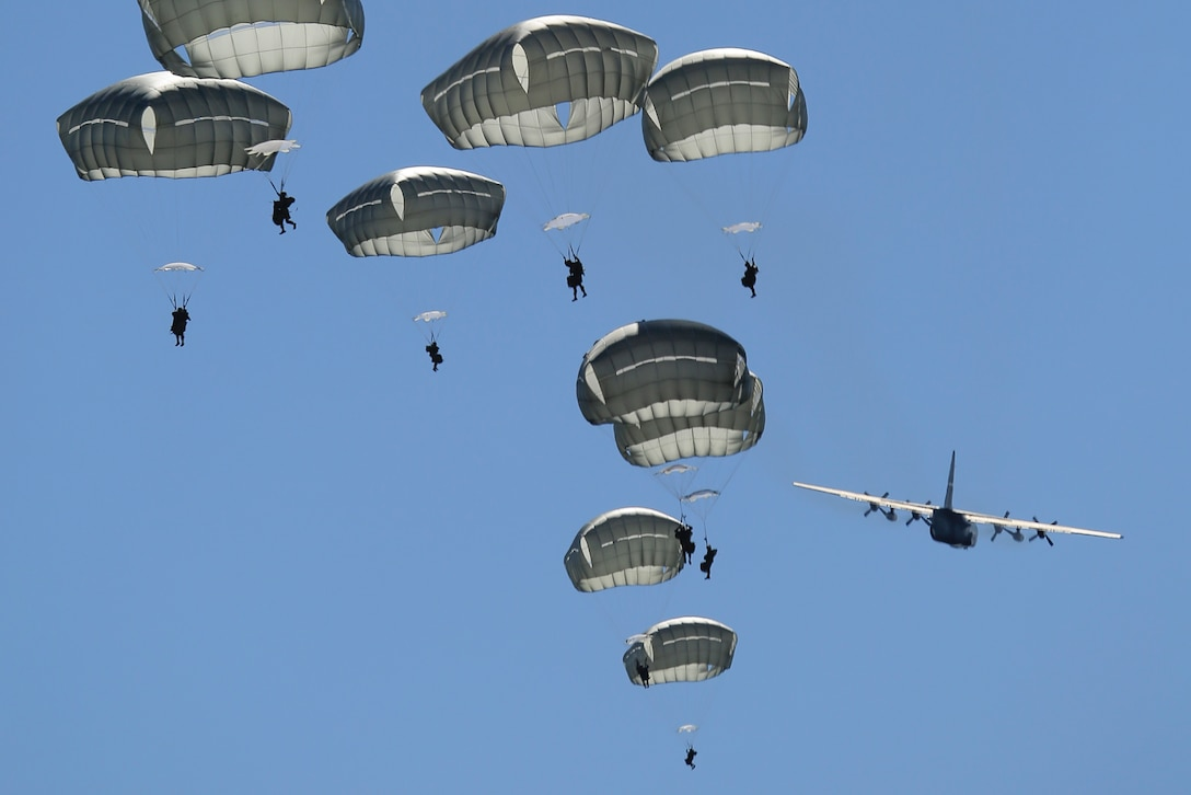 Paratroopers assigned to 1st Battalion (Airborne), 501st Infantry Regiment descend after jumping out of a C-130 Hercules, assigned to the 374th Wing from Yokota Air Base, Japan, over the Malemute drop zone at Joint Base Elmendorf-Richardson, Alaska, Aug. 24, 2015. Japanese Ground Self-Defense Force and Army paratroopers conducted the practice jump utilizing Royal Australian and U.S. Air Force aircraft as part of Pacific Airlift Rally 2015. The exercise is a biennial, multilateral tactical military symposium designed to enhance military airlift interoperability and cooperation between nations of the Pacific region for future humanitarian missions. (U.S. Air Force photo/Alejandro Pena)
