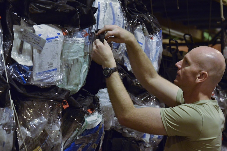 Capt. Brandon Trappett, 379th Expeditionary Medical Group Mobile Field Surgical Team, searches for the correct medical supplies for his team to complete a timed setup and equipment familiarization training August 28, 2015 at Al Udeid Air Base, Qatar. (U.S. Air Force photo/Staff Sgt. Alexandre Montes)
