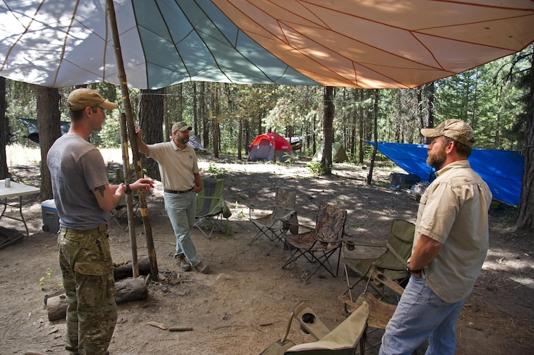 Rick Hall, an Air Force liaison to the U.S. Forest Service, and Todd Foster, the 336th Training Group training area manager, speak with a survival, evasion, resistance and escape specialist July 29, 2015, at Colville National Forest, Wash. Foster and Hall complete walk throughs at instructor camps to ensure they are within Forest Service standards. (U.S. Air Force photo/Airman 1st Class Nicolo J. Daniello)