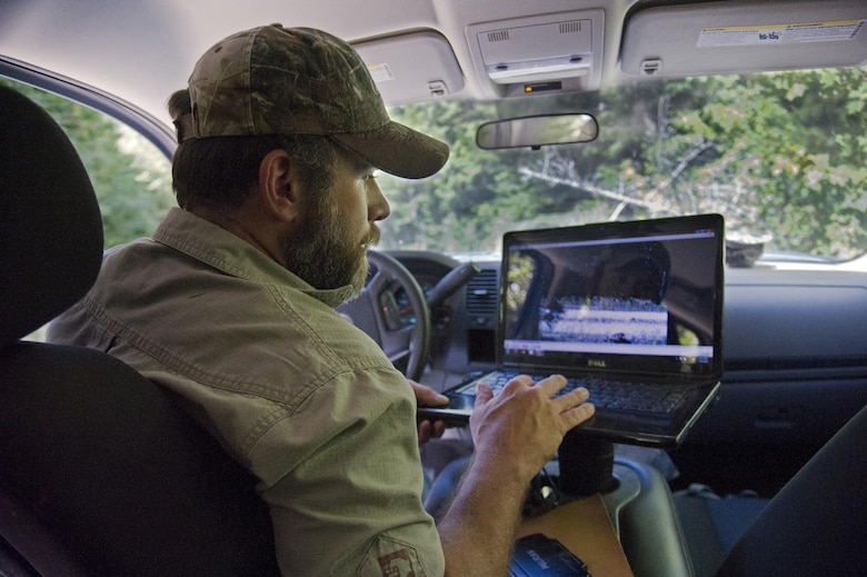 Todd Foster, the 336th Training Group training area manager, watches a video recorded with a Bushnell trail camera July 29, 2015, at Colville National Forest, Wash. Foster has a laptop with video playback capabilities so he can watch video recordings of tracked animals on site. (U.S. Air Force photo/Airman 1st Class Nicolo J. Daniello)