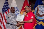 Byron Davis is presented the DLA Meritorious Service Award by DLA Distribution Commander Army Brig. Gen. Richard Dix for performing CPR on a co-worker exhibiting signs of a heart attack.